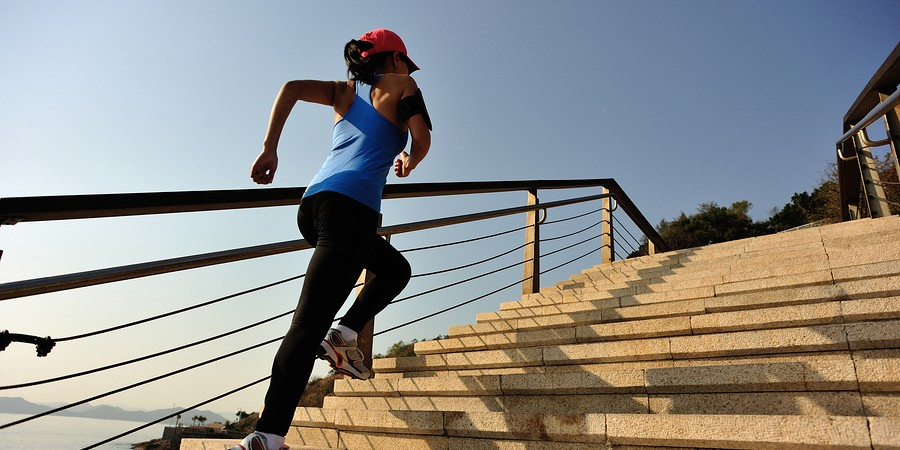 healthy lifestyle sports woman running up on stone stairs sunris